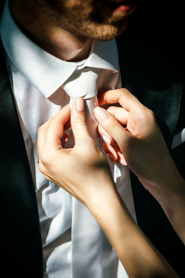 Woman corrects the men tie stock photo