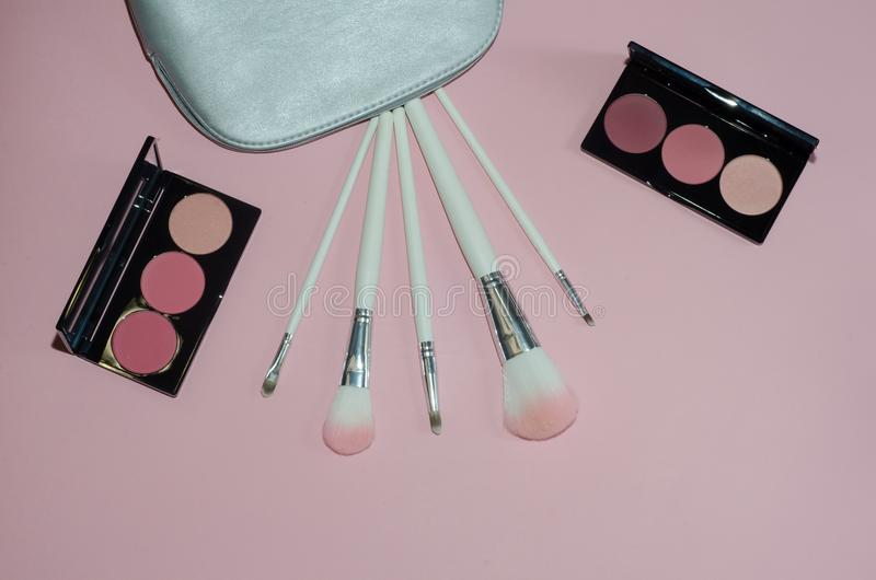 Woman cosmetic bag, make up beauty products on pink background. Makeup brushes and rouge palettes. Decorative cosmetics. Top view, stock images