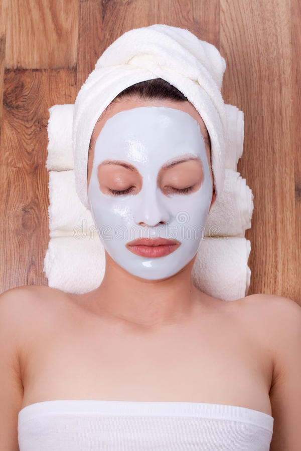 Woman with cosmetic mask on her face stock photography
