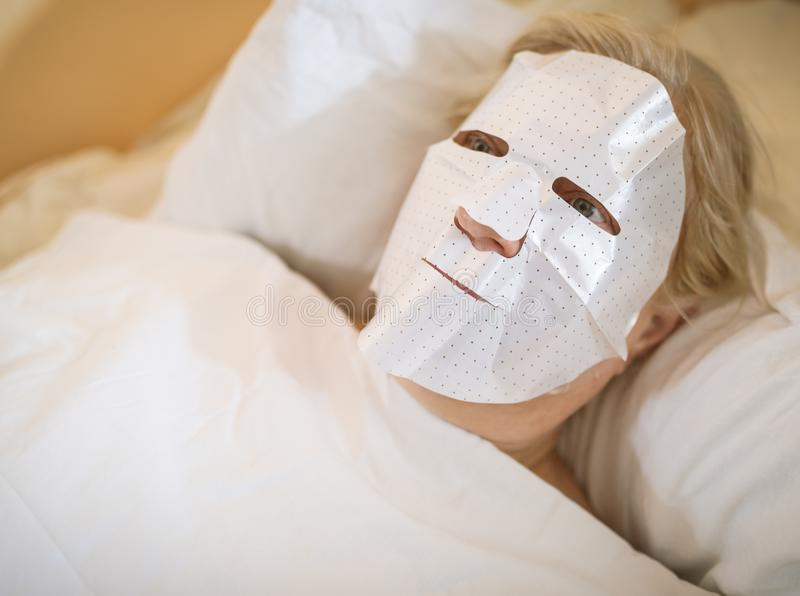 Woman with a cosmetic mask. Woman with a cosmetic mask at home royalty free stock image