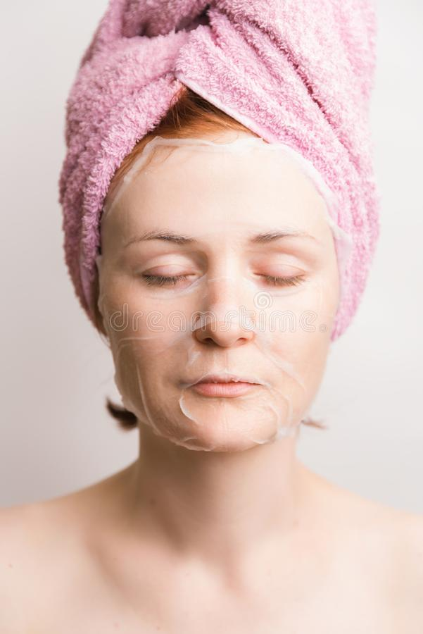 Woman with cosmetic tissue mask on face on light background stock photography