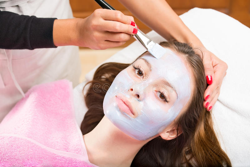 Woman with cosmetology mask. Young pretty women looking at camera while laying on couch being treated by cosmetologist, applying blue cosmetology mask to her stock photo