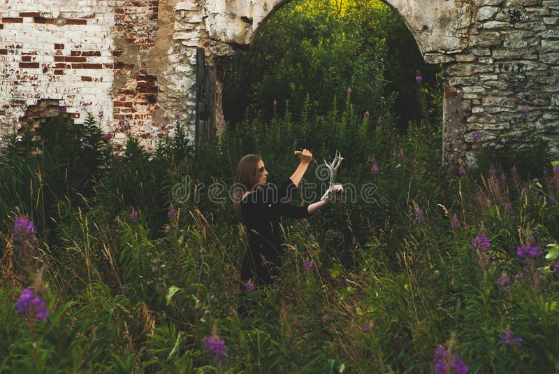Woman cosplay a witch conducting an ominous rite among the ruins. Woman cosplay a witch conducting an ominous rite with a deer skull among the ruins stock photos