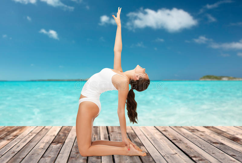 Woman in cotton underwear doing yoga exercise. People, health and wellness concept - woman in cotton underwear doing yoga exercise on wooden floor over sea and stock photo