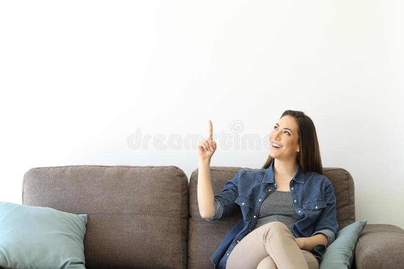 Woman on a couch pointing above. Happy woman sitting on a couch pointing above at a white isolated wall stock image