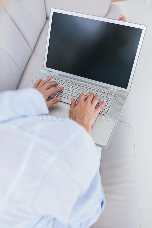 Woman on couch typing on laptop. At home in the living room stock images