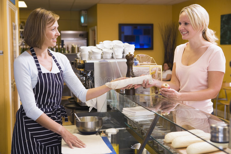 Woman at counter in restaurant serving customer stock photography