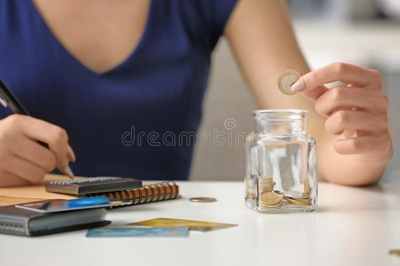 Woman counting coins at table. Savings concept royalty free stock photography
