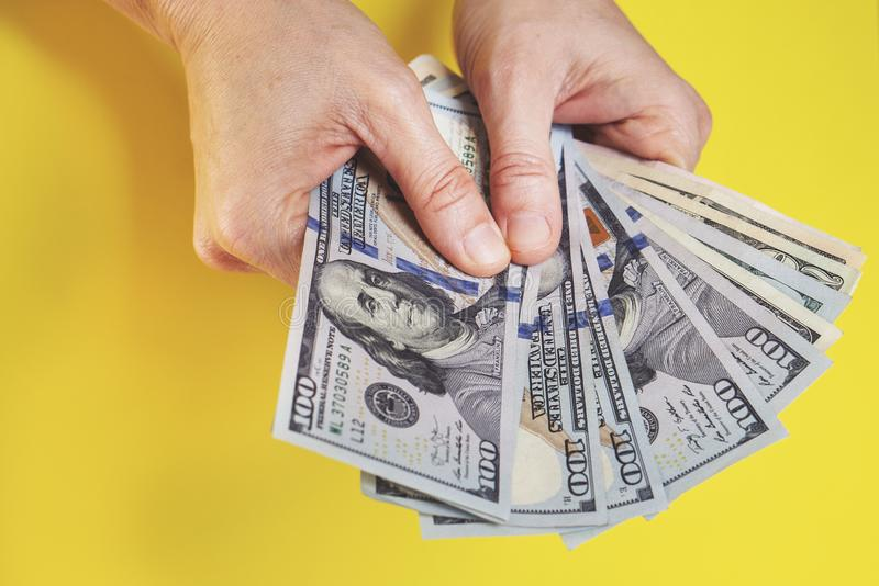 Woman counting money, economy concept, allocation of money. Woman counting money, economy concept and allocation of money, yellow bcakground stock photography