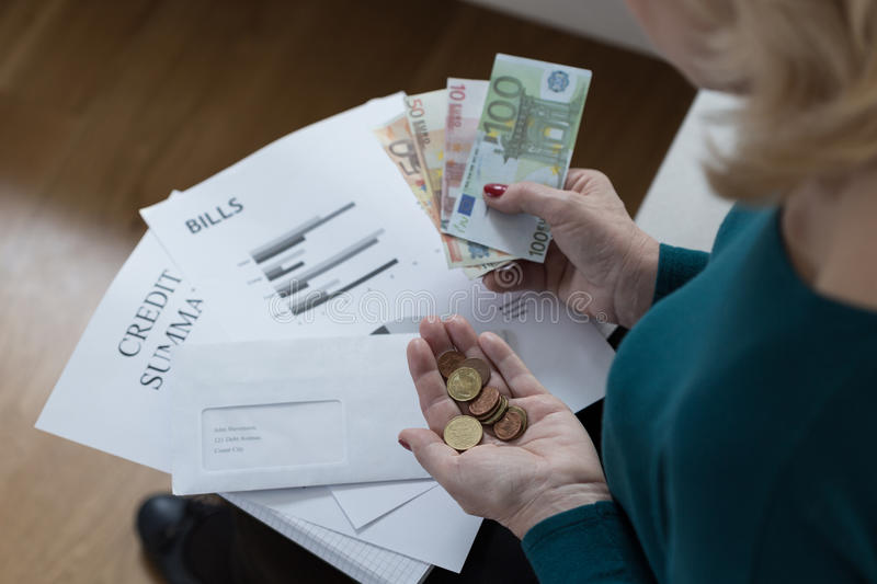 Woman counting money. Elderly woman counting money and solving financial difficulties royalty free stock photos