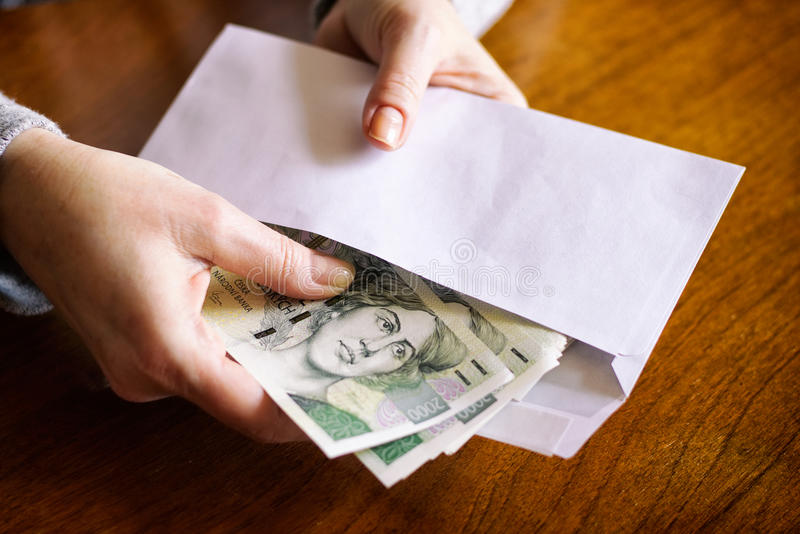 Woman counting money. Money in an envelope as a symbol of corruption. Taking bribes, Czech currency in criminal activity. Woman gives bribes to the envelope stock photography