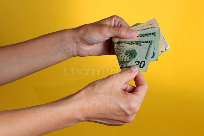 Woman counting money on yellow texture. Woman counting money on yellow background stock photography