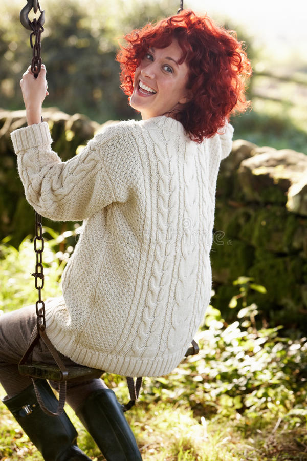 Woman on country garden swing. Smiling at camera royalty free stock image