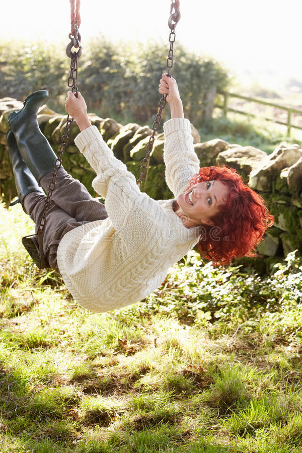 Woman on country garden swing. Smiling stock image
