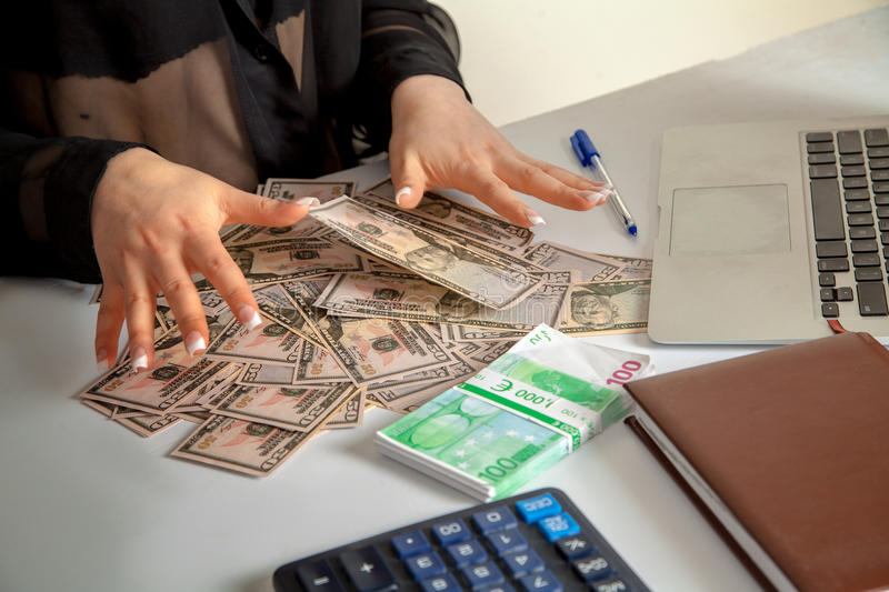 Woman counts a lot of money. Female counts a lot of money on the table. horizontal photo of a lot of money royalty free stock photo
