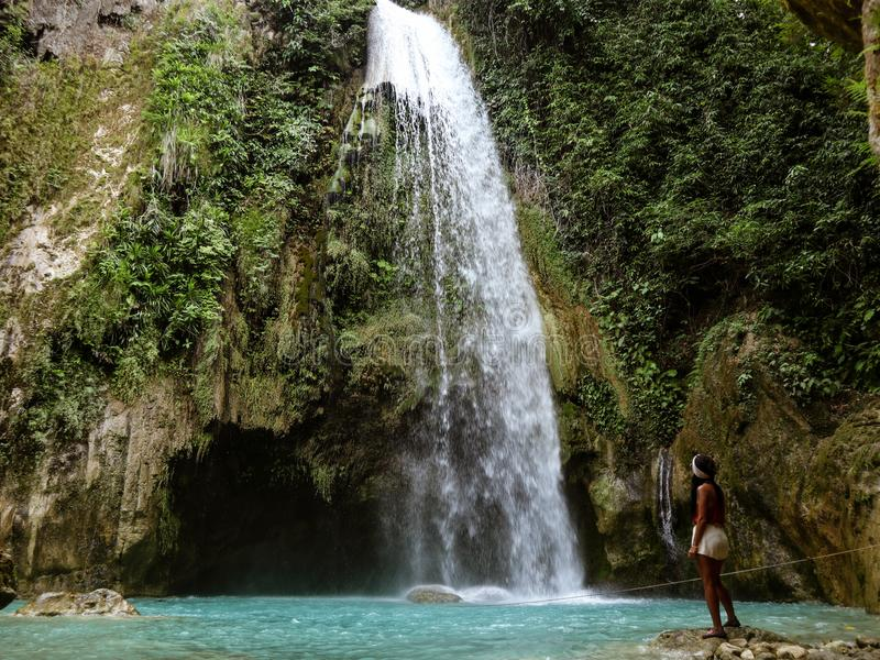 Woman couple alone in deep forest waterfall, inambakan falls in Cebu Island in Philppines. Woman alone in deep forest waterfall from mountain gorge at hidden stock photo