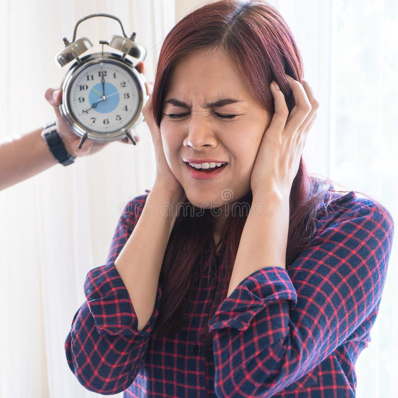 Woman cover her ear from stress out by Alarm clock sound. Woman cover her ear from stress out by Alarm clock deadline sound stock images