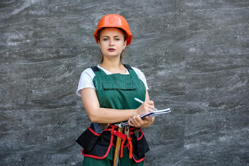 Woman in coverall and helmet holding notepad and posing for camera on grey background.  stock images