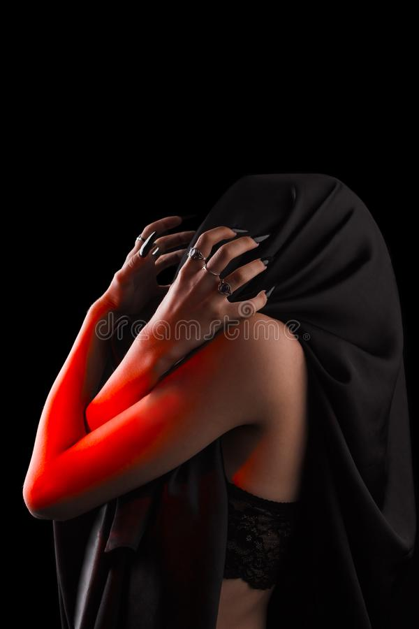 A woman covered with black cloth with a closed face suffers. faceless pain. long black nails on thin female fingers. emotion stock photos