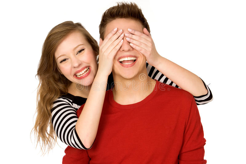 Woman covering boyfriend's eyes stock image