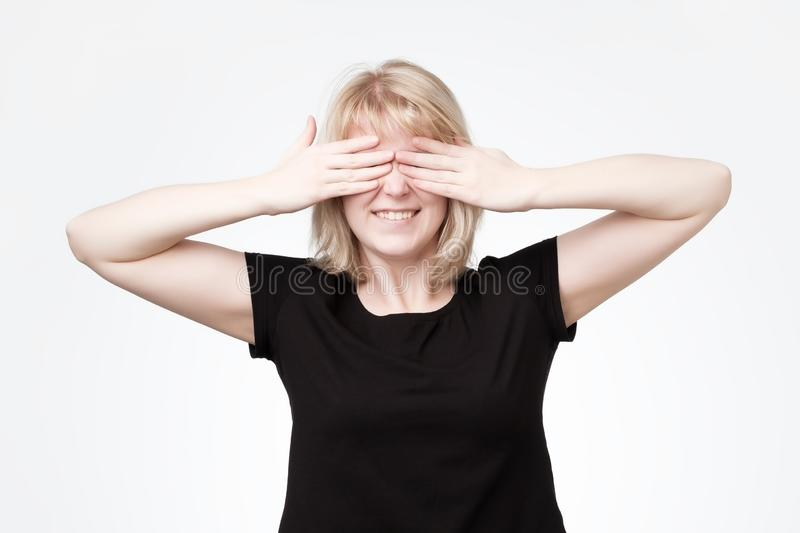Woman covering eyes with hands and smiling broadly, being intrigued while waiting for surprise. Emotive positive european woman covering eyes with hands and royalty free stock photography