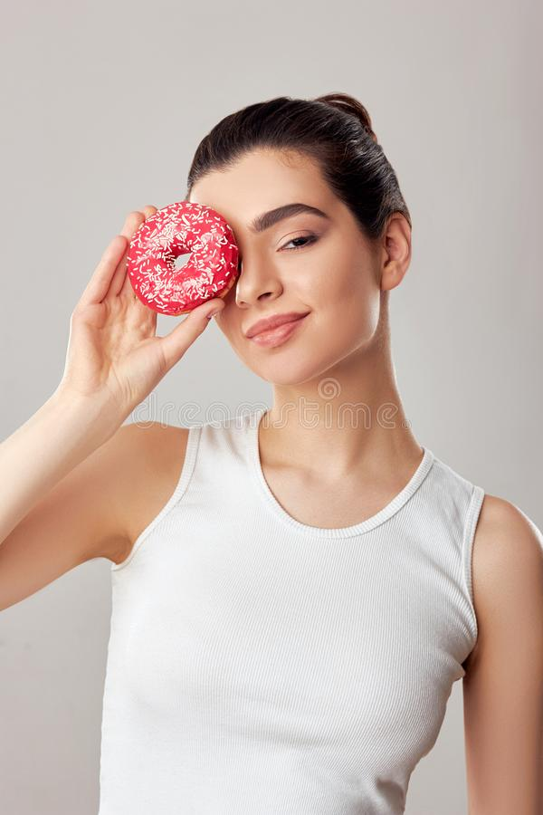 Woman covering her eye with donut over pink donut. Diet. Brunette girl tastes a donut. stock photo