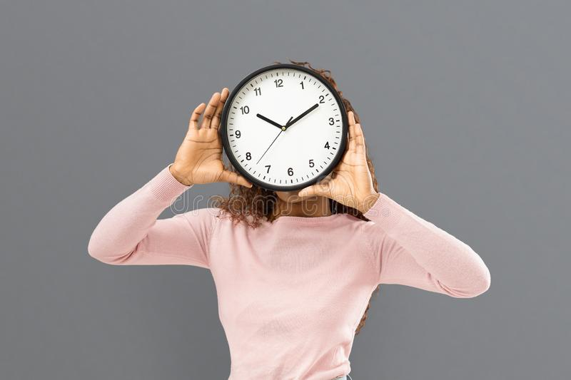 Woman covering her face with big watch. Time management concept. Young mixed race woman covering her face with big watch on grey background stock photography