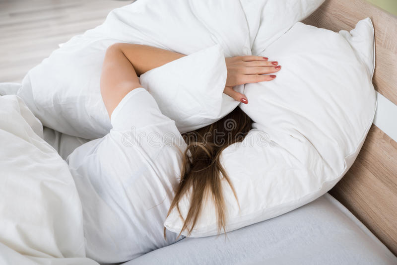 Woman Covering Her Head With Pillow royalty free stock photo