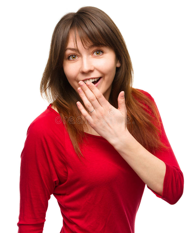 Woman is covering her mouth in astonishment. Young woman is covering her mouth in astonishment, isolated over white stock photography
