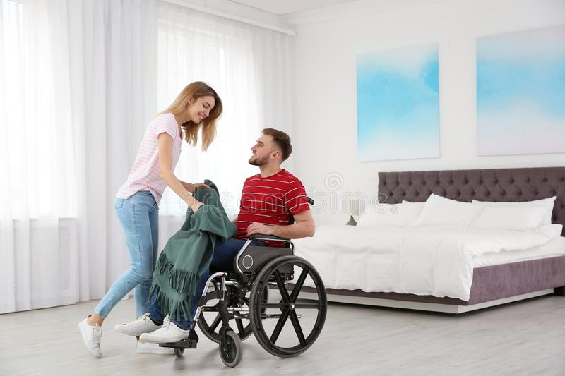 Woman covering man in wheelchair with plaid. Helping disabled. Woman covering men in wheelchair with plaid at home. Helping disabled royalty free stock photography