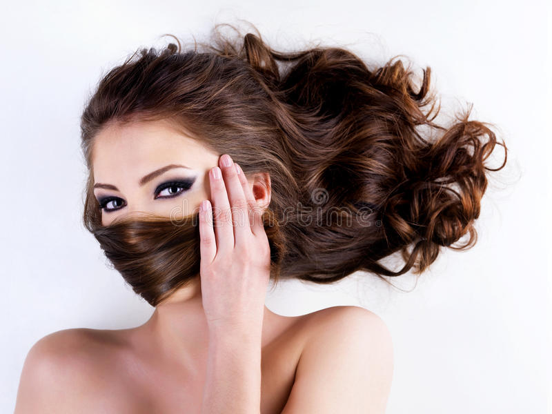 Woman covers the face by hairs stock photography