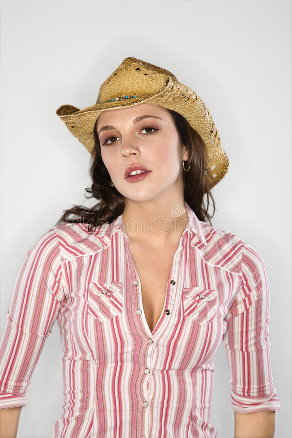 Woman in cowboy hat. Young Caucasian woman wearing cowboy hat looking at viewer stock image