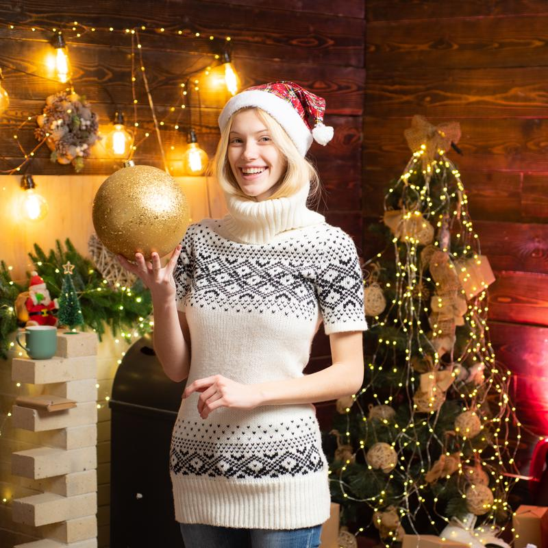 Woman cozy knitted sweater enjoy christmas atmosphere at home. Girl winter clothes santa claus hat celebrate christmas royalty free stock photo