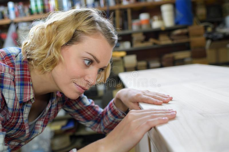 Woman craftsperson working on workbench in workshop royalty free stock image