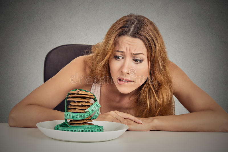 Woman craving sugar sweet cookies but worried about weight gain. Portrait young unhappy woman craving sugar sweet cookies but worried about weight gain sitting royalty free stock image