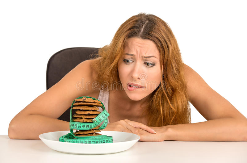 Woman craving sugar sweet cookies but worried about weight gain. Portrait young unhappy woman craving sugar sweet cookies but worried about weight gain sitting stock images