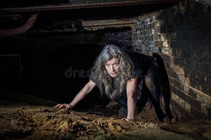 Woman crawling in Derelict Building royalty free stock image