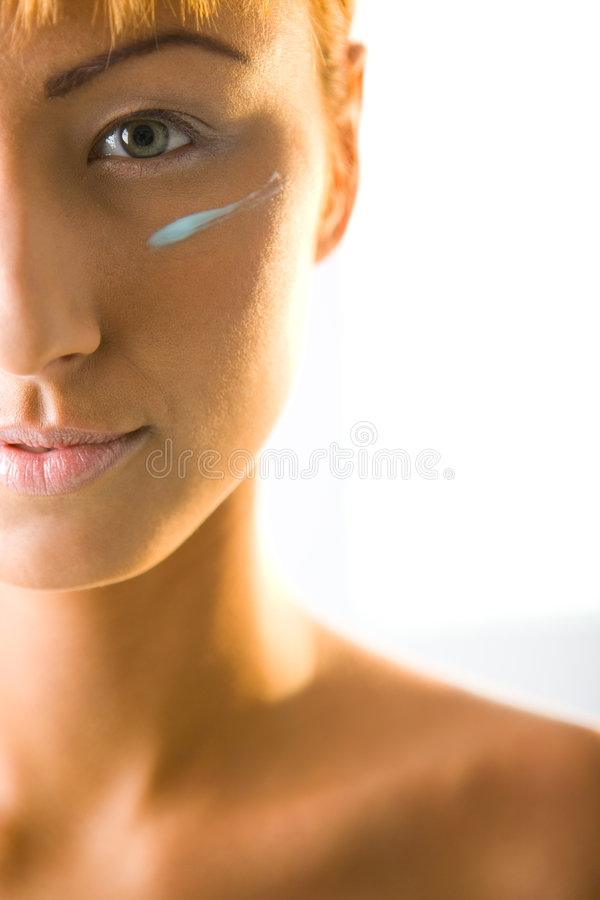 Woman with cream on face stock images