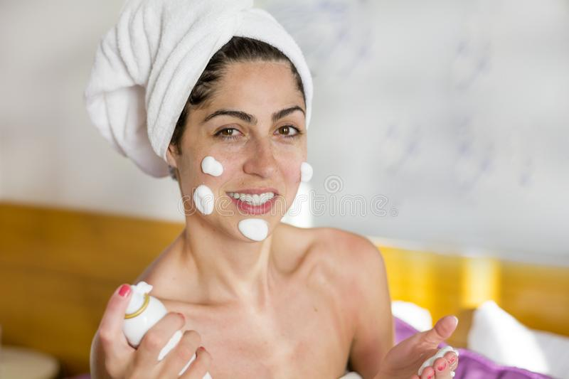 Woman with Cream on her Face. Smiling young woman applying cream on her face royalty free stock images