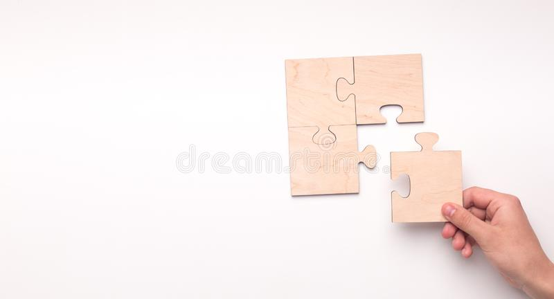 Woman creating picture with missing piece of wooden puzzle. On white panorama background with copy space royalty free stock photos