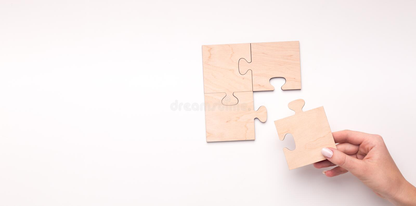 Woman creating wooden puzzle of four pieces with copy space. For text on white background, panorama royalty free stock photo