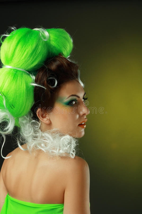 Woman with creative green hairstyle. Beautiful fashionable smiling young women with creative hairstyle with green false hairs and art make up royalty free stock images