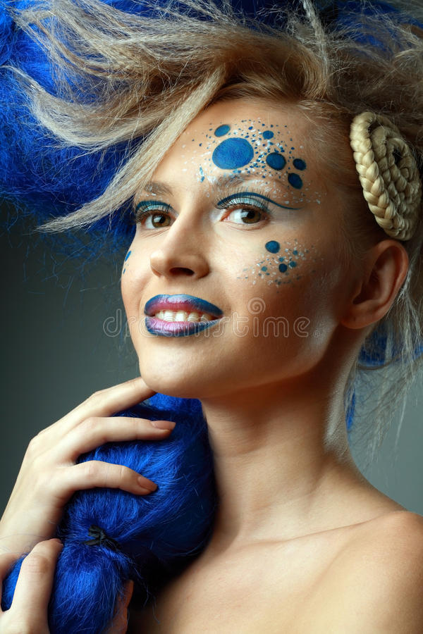 Woman with creative hairstyle. Beautiful fashionable smiling young women with creative hairstyle with blue hairs and art make up stock photo