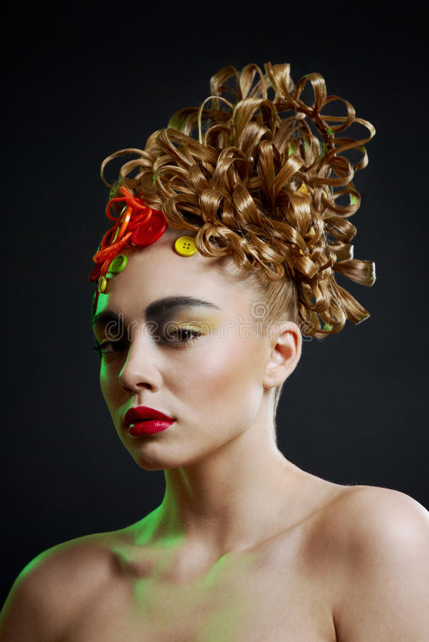 Woman with creativity hairstyle with colored butto