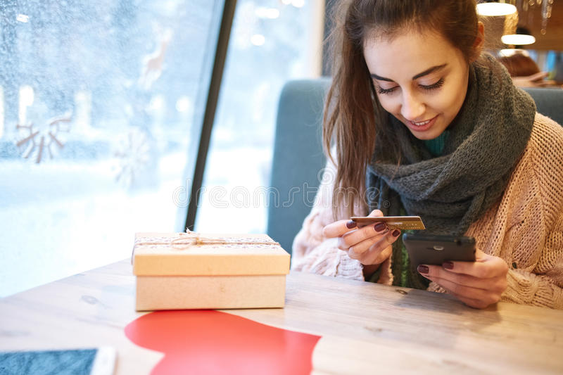 Woman with credit card and phone. Smiling woman with credit card and phone. gift box and red paper heart on the wooden table stock image