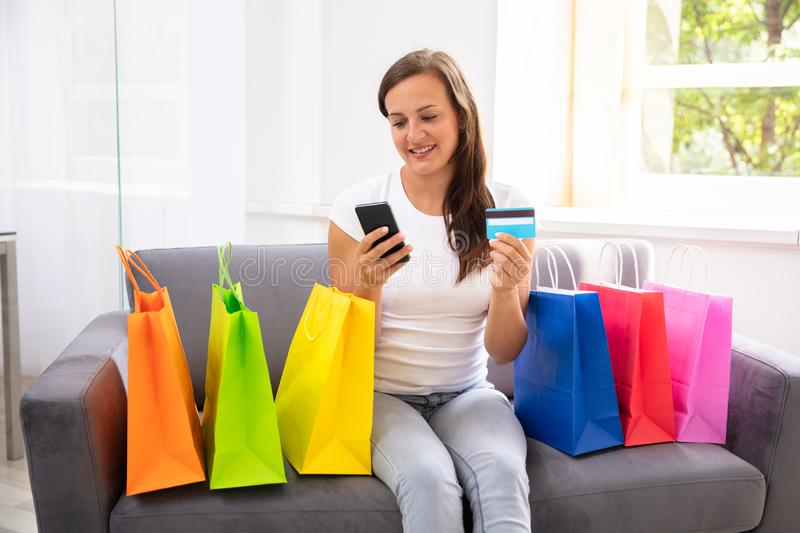 Woman With Credit Card Shopping Online On Cellphone. Woman With Credit Card Sitting On Sofa Shopping Online On Cellphone royalty free stock photos
