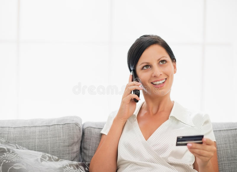Woman with credit card and speaking mobile phone