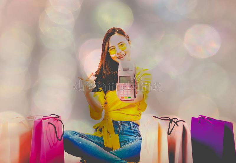 Woman with credit card swiping machine & shopping bags on table. payment with nfc technology. Woman with credit card swiping machine & shopping bags on table royalty free stock images