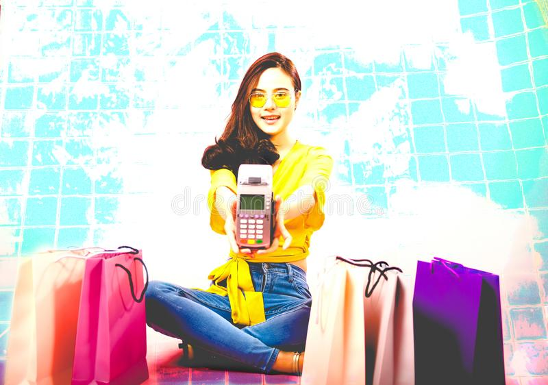 Woman with credit card swiping machine & shopping bags on table. payment with nfc technology. Woman with credit card swiping machine & shopping bags on table stock image