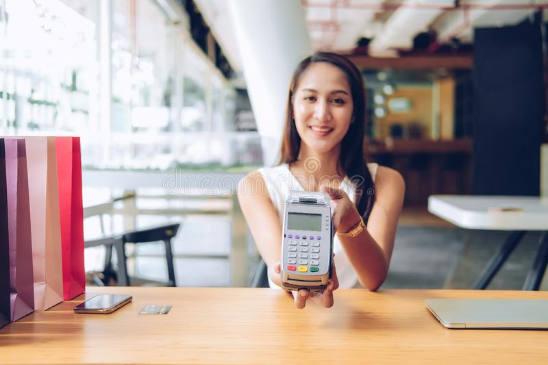 Woman with credit card swiping machine & shopping bags on table. payment with nfc technology. Woman with credit card swiping machine & shopping bags on table stock photo